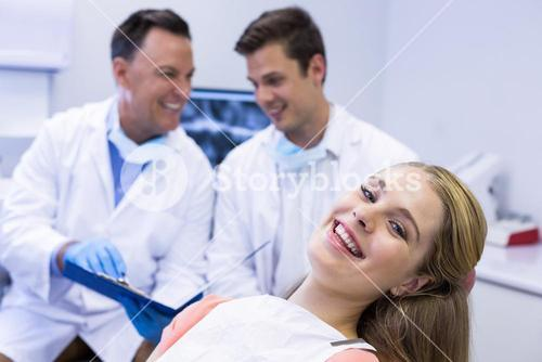 Portrait of smiling female patient sitting on dental chair
