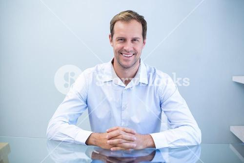 Portrait of happy dentist sitting at desk