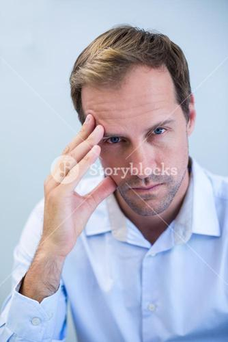 Portrait of tensed dentist sitting with hand on forehead