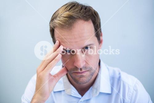 Portrait of tensed doctor with hand on forehead