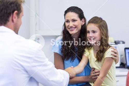 Dentist shaking hand with daughter after dental examination