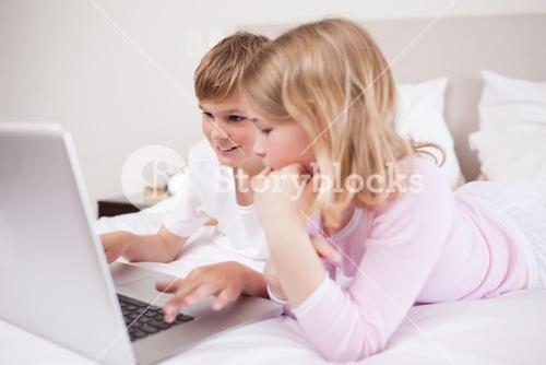 Smiling children using a laptop