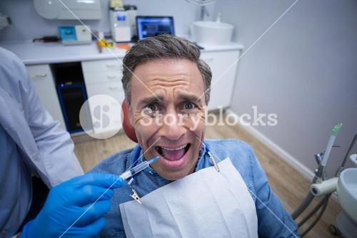 Dentist injecting anesthetics in scared male patient mouth