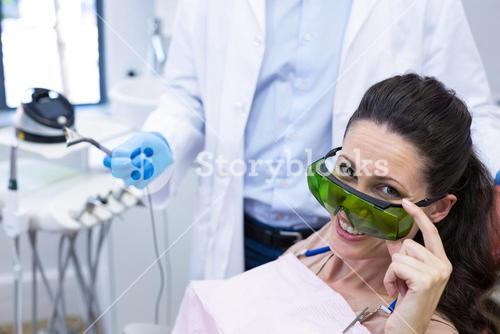 Smiling female patient sitting on dentist chair