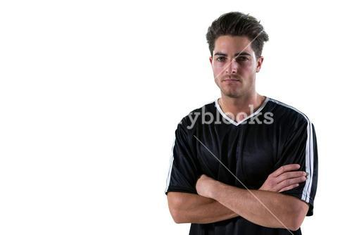 Portrait of football player standing with arms crossed