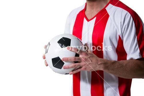 Mid-section of football player holding football with both hands