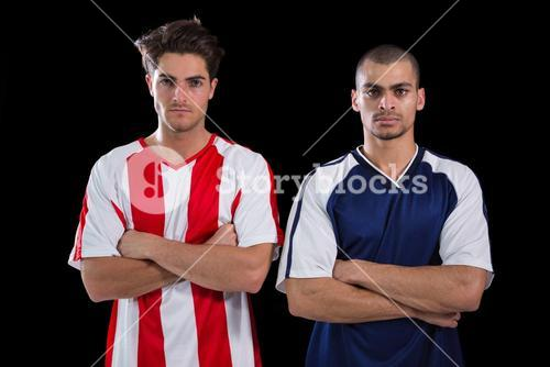 Two football players standing with arms crossed