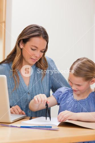 Portrait of a woman helping her daughter doing her homework