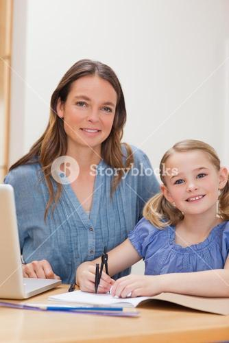 Portrait of a beautiful woman helping her daughter doing her homework