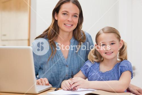 Beautiful woman helping her daughter doing her homework