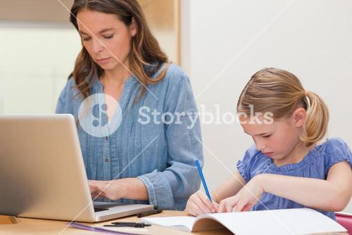 Girl doing her homework while her mother is using laptop