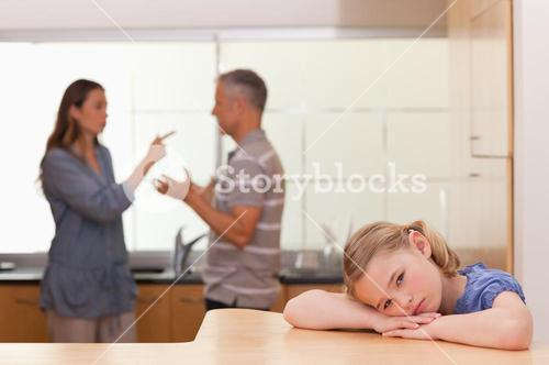 Sad little girl listening her parents having an argument