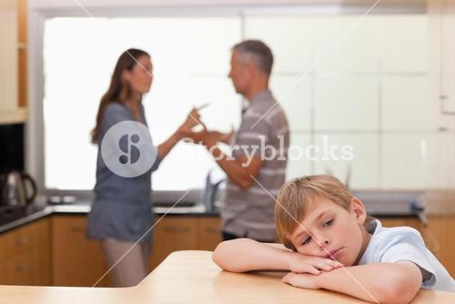 Sad little boy hearing his parents arguing