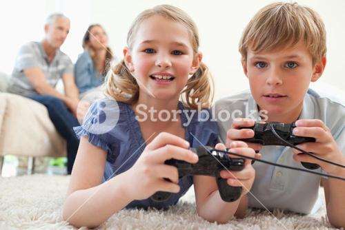 Playful siblings playing video games with their parents on the background