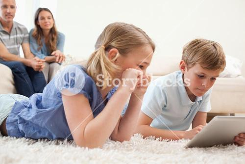 Children using a tablet computer with their parents on the background