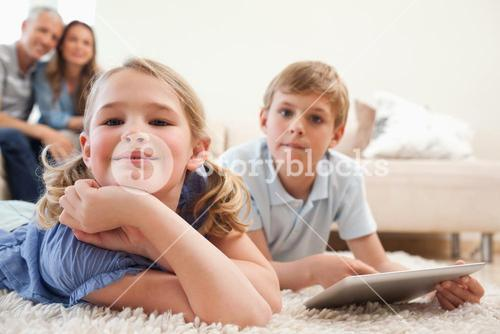Happy siblings using a tablet computer with their parents on the background