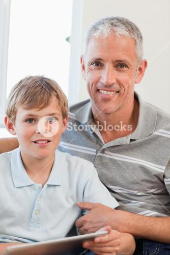 Portrait of a delighted father and his son using a tablet computer