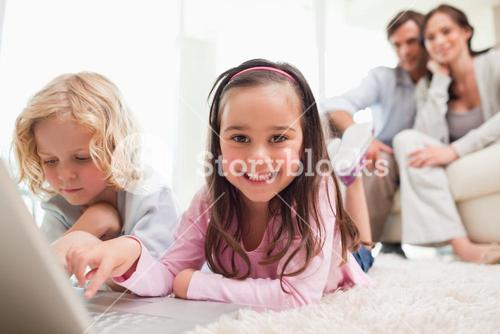 Siblings using a laptop while their parents are in the background