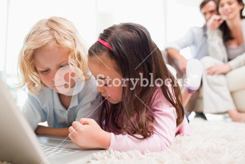 Siblings using a notebook while their parents are in the background