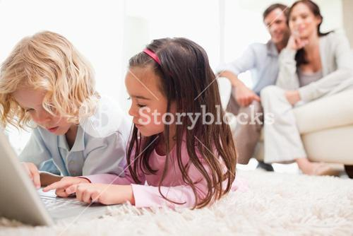 Children using a notebook while their parents are in the background