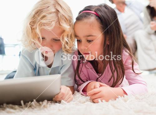 Children using a tablet computer while their parents are in the background