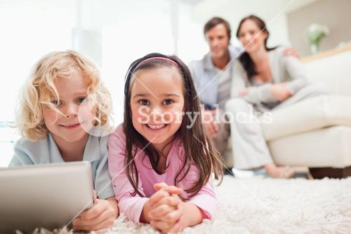 Siblings using a tablet computer while their parents are in the background