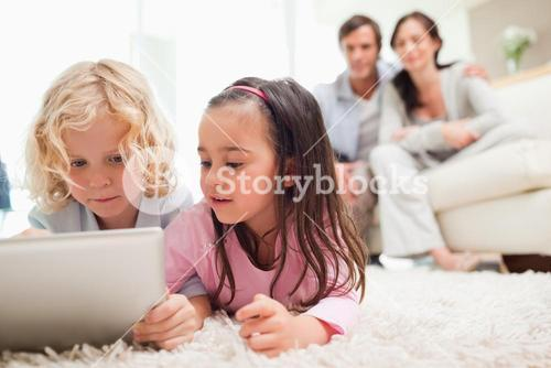 Cute siblings using a tablet computer while their parents are in the background