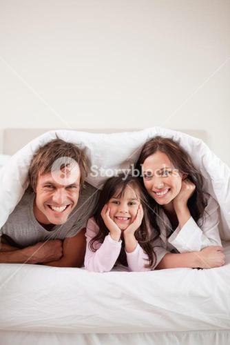 Portrait of parents lying under a duvet with their daughter