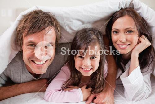 Happy parents lying under a duvet with their daughter