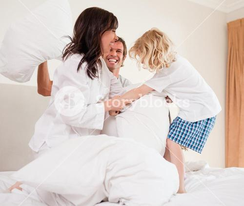 Cheerful family having pillow fight