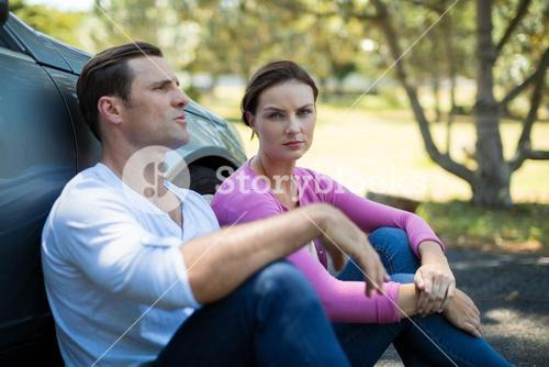 Tired couple sitting by breakdown car