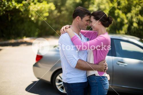 Couple embracing by car on sunny day