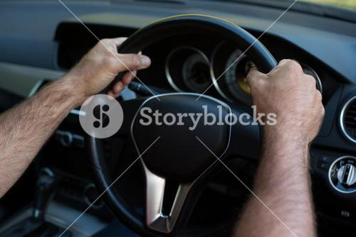 Hands of person driving car