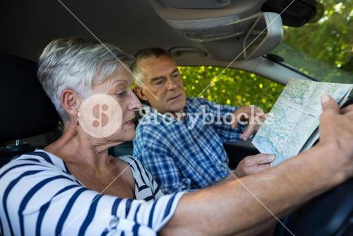 Senior couple reading map in car