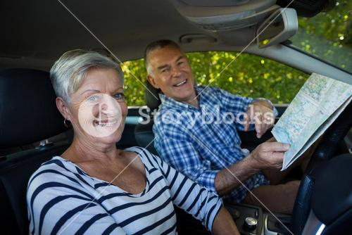 Senior couple with road map in car