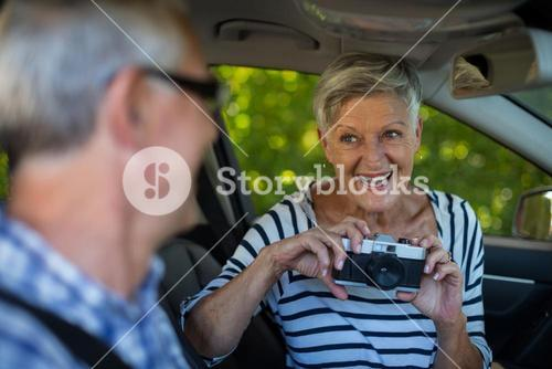 Senior woman photographing man in car