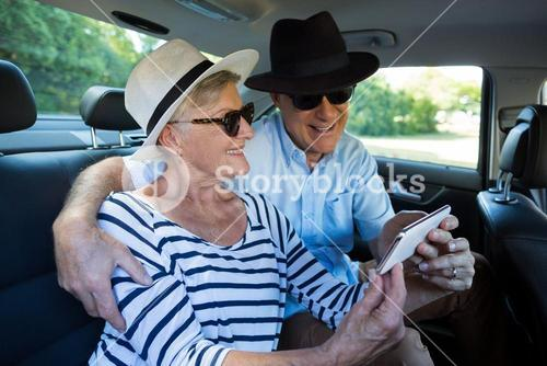 Senior couple taking selfie on car back seat