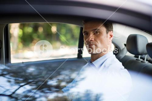 Confident man sitting on car back seat