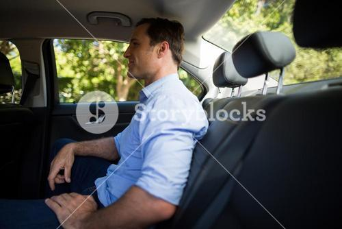 Young man sitting on back seat in car