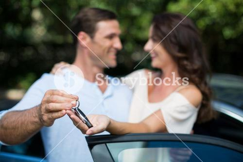 Man giving key to woman by car