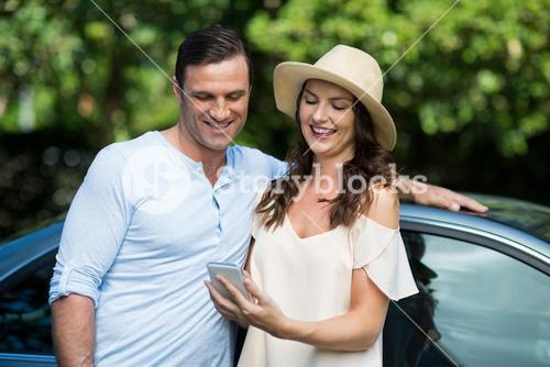 Young woman holding mobile with man by car