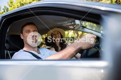 Cheerful couple sitting in car
