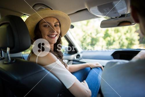 Smiling young woman sitting with man in car