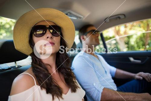 Couple wearing sunglasses traveling in car