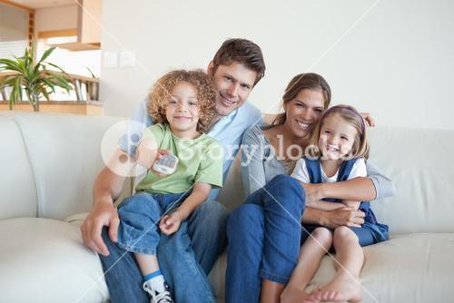 Smiling family watching TV together