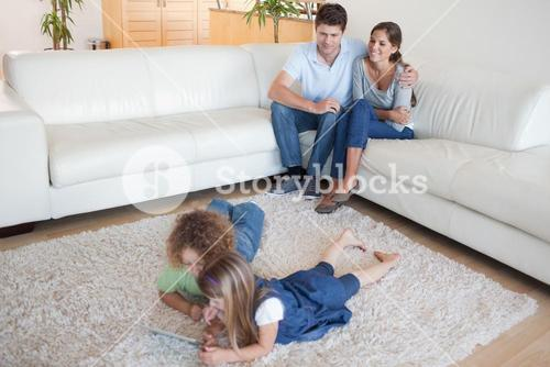 Children using a tablet computer while their happy parents are watching