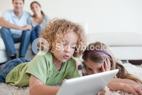 Young children using a tablet computer while their happy parents are watching
