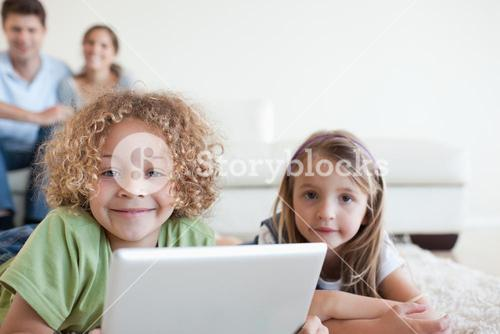 Smiling children using a tablet computer while their happy parents are watching