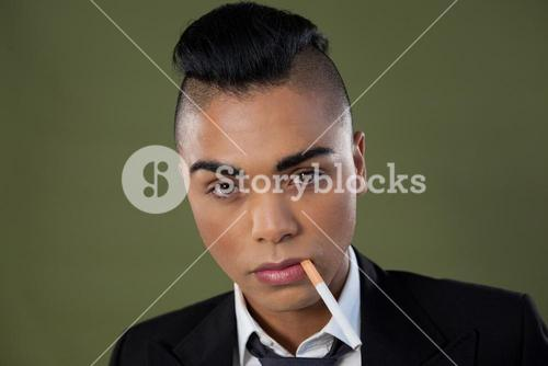 Transgender woman with cigarette in mouth over green background