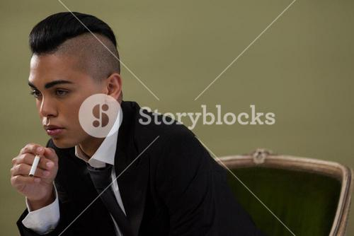 Transgender woman holding cigarette while sitting on chair